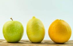 Limón, manzana, anaranjada en un fondo blanco Imagen de archivo libre de regalías