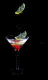 Limón que cae en el vidrio de martini foto de archivo