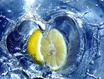 Limón que salpica el agua imagen de archivo