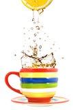Limón, taza del color y chapoteo del té Foto de archivo libre de regalías
