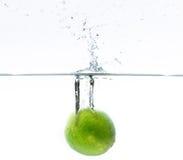 Limón verde que cae en el agua Imágenes de archivo libres de regalías