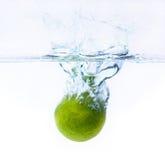 Limón verde que cae en el agua Imagenes de archivo