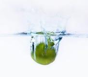 Limón verde que cae en el agua Foto de archivo libre de regalías
