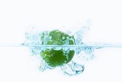 Limón verde que cae en el agua Imagen de archivo libre de regalías