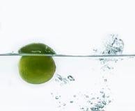 Limón verde que cae en el agua Imagen de archivo