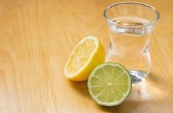 Limón y cal cerca del vidrio con el agua potable En la tabla foto de archivo