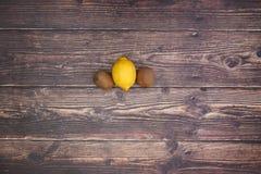 Limón y 2 kiwis en la tabla de madera fotografía de archivo