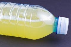 limón y zumo de naranja Mano-exprimidos en una botella Fotografía de archivo