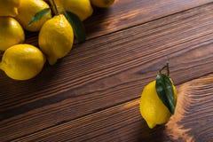Limões amarelos suculentos frescos com as folhas na tabela de madeira foto de stock