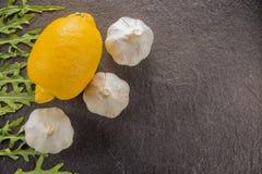 Limões com alho em um fundo de pedra preto Imagem de Stock Royalty Free