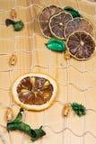 Limões e cais secos na rede branca e na placa de madeira Foto de Stock