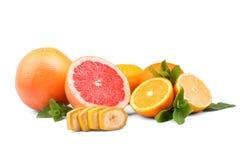 Limões e cal Laranjas, toranjas, limão fresco e fatias de banana com folhas do citrino, isolados em um fundo branco Fotografia de Stock