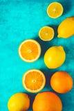 Limões e laranjas no vertical ciano do fundo fotografia de stock royalty free