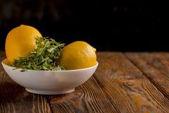 Limões e rúcula em uma tabela de madeira Imagens de Stock