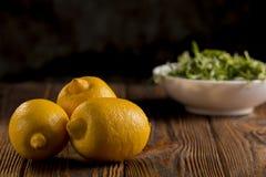 Limões e rúcula em uma tabela de madeira Imagem de Stock