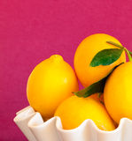 Limões em uma bacia branca com fundo magenta Imagens de Stock