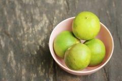 Limões em uma bacia cor-de-rosa em um fundo de madeira Foto de Stock
