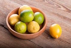 Limões em uma bacia em uma tabela Fotos de Stock Royalty Free