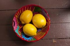 Limões em uma bacia vermelha Imagem de Stock Royalty Free