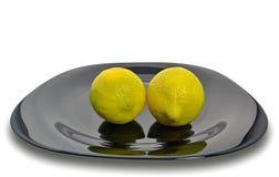 Limões em uma placa preta Fotografia de Stock Royalty Free