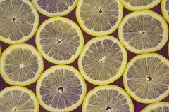 Limões frescos em um fundo roxo fotos de stock royalty free