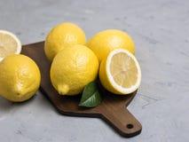 Limões inteiros e cortados na placa de corte de madeira Citrinas frescas orgânicas imagens de stock