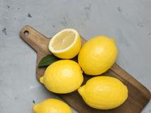 Limões inteiros e cortados na placa de corte de madeira Citrinas frescas orgânicas, vista superior, espaço da cópia fotos de stock