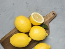Limões inteiros e cortados na placa de corte de madeira Citrinas frescas orgânicas, vista superior, espaço da cópia fotografia de stock royalty free