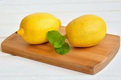 Limões na placa de desbastamento Fotografia de Stock Royalty Free