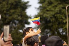 Lima, Lima/Perù - 2 febbraio 2019: Bambino che iscena bandiera venezuelana nella protesta contro Nicolas Maduro immagine stock libera da diritti