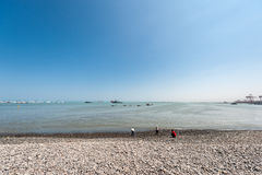 LIMA, PERÚ - 12 DE ABRIL DE 2013: Costa costa del océano de South Pacific con las naves y los yates Tres personas en orilla Imagenes de archivo