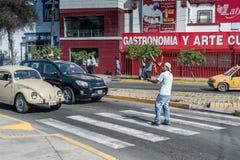 LIMA, PERÚ - 15 DE ABRIL DE 2013: Funcionamiento de la calle El jugar con el fuego delante del coche Lima, Perú Fotos de archivo libres de regalías