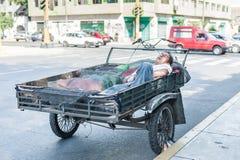 LIMA PERU - APRIL 15, 2013: Den peruanska mannen sover i motorcykel i Lima, Peru fotografering för bildbyråer
