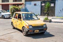 LIMA PERU - APRIL 12, 2013: Gammal gul taxibil i Lima Street Gammal chaufför med kvinnapassanger fotografering för bildbyråer