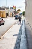 LIMA PERU - APRIL 12, 2013: Gata och pojke som går med skateboarden på trottoaren royaltyfri foto