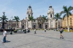 LIMA PERU - APRIL 15, 2013: Lima Cathedral och några turist- flygfåglar i bakgrund arkivfoton