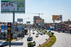 LIMA PERU - APRIL 12, 2013: Lima City Street med motorwayen och trafik för två vägar arkivbild