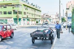 LIMA PERU - APRIL 15, 2013: Personen sover i gatan En man går vid motorcykeln Siestatid arkivfoton