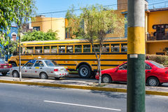 LIMA, PERU - APRIL 12, 2013: School bus waiting in Lima Street with Taxi and other crazy drivers. School bus waiting in Lima Royalty Free Stock Images