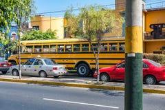 LIMA PERU - APRIL 12, 2013: Skolbuss som väntar i Lima Street med taxien och andra galna chaufförer royaltyfria bilder