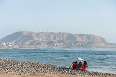 LIMA, PERU - APRIL 14, 2013: South Pacific Ocean coast in Miraflores, Lima, Peru. Local People and mountain in Background. Royalty Free Stock Photos