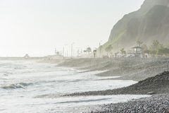 LIMA, PERU - APRIL 14, 2013: South Pacific Ocean coast in Miraflores, Lima, Peru. Mountain Local People and tourists in Background Stock Photos