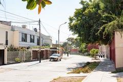 LIMA, PERU - 12 DE ABRIL DE 2013: Rua com os meninos de escola no fundo em árvores verdes Imagens de Stock Royalty Free
