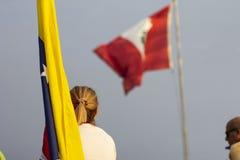 Blonde woman looking at Peruvian flag while holding Venezuelan flag stock photo