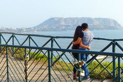 Young couple kissing in front of Pacific view, Lima, Peru stock images