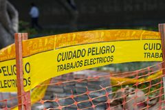 Yellow tape marked caution `cuidado` in Spanish royalty free stock photo