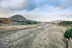 Lima/Peru - 07 18 2017: Trockene und schmutzige Unterseite des Rimac-Flusses herein in die Stadt lizenzfreie stockfotografie