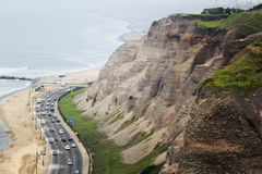 Lima's coastline on a foggy day. Cars on a busy road next to the hills in Miraflores in Lima stock photography