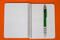 Ślimakowaty notatnik z zielonym piórem Obrazy Stock