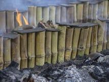 Limaktiga ris som grillas i bambu Arkivfoton
